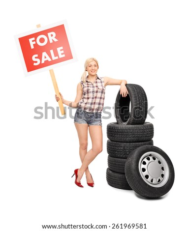 Full length portrait of a young woman standing next to a pile of tires and holding a red for sale sign isolated on white background - stock photo