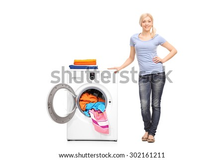 Full length portrait of a young woman standing next to a washing machine and looking at the camera isolated on white background - stock photo