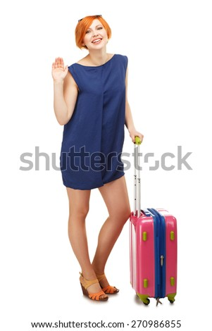 Full length portrait of a young woman standing with a pink travel suitcase and waving goodbye, isolated on white background - stock photo