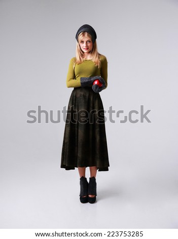 Full length portrait of a young woman standing with apple on gray background - stock photo