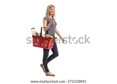 Full length portrait of a young woman walking and carrying a shopping basket full of groceries isolated on white background - stock photo