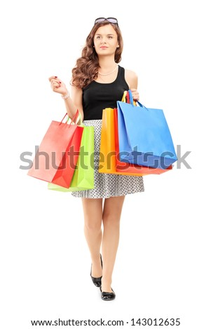 Full length portrait of a young woman walking with shopping bags, isolated on white background - stock photo