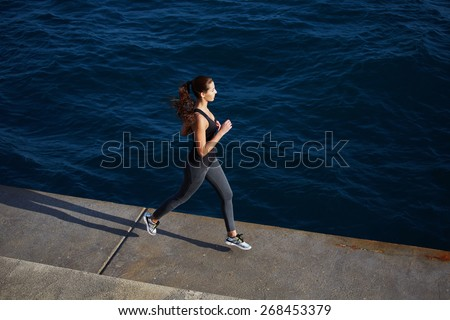 Full length portrait of a young woman with fitness body running at the seaside next to the ocean, athletic girl jogging over amazing big waves background at sunny day - stock photo
