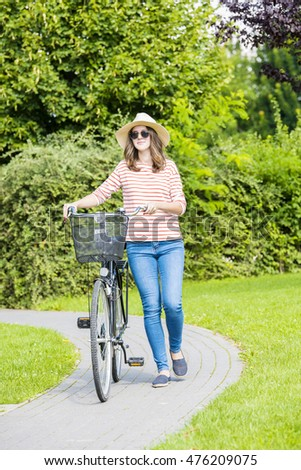 Full length portrait of a young woman with her bike in the park. Smiling female wearing a straw hat and sunglasses while pushing vintage bicycle.