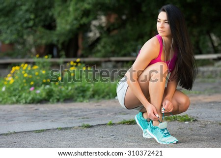 Full length portrait of active jogging female runner, with long dark hair, preparing shoes for training and working out at fitness park - stock photo