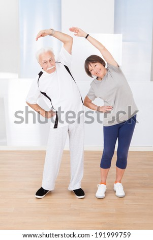 Full length portrait of active senior couple doing stretching exercise at gym - stock photo