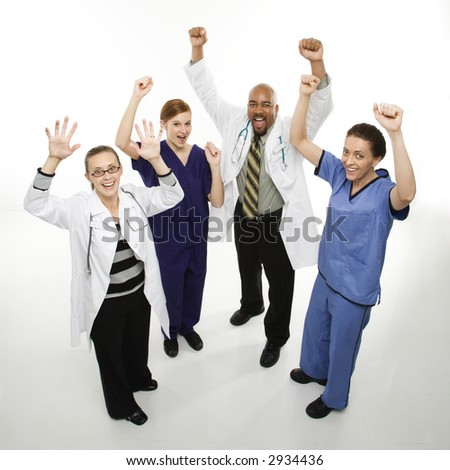 Full-length portrait of African-American man and Caucasian women medical healthcare workers in uniforms cheering with arms raised standing against white background. - stock photo