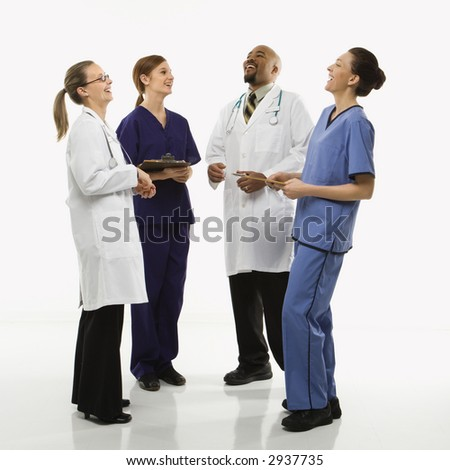 Full-length portrait of African-American man and Caucasian women medical healthcare workers in uniforms laughing standing against white background. - stock photo