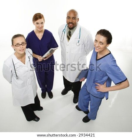 Full-length portrait of African-American man and Caucasian women medical healthcare workers smiling in uniforms standing against white background. - stock photo