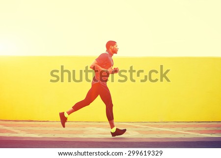 Full length portrait of afro american runner with muscular body in tracksuit jogging against yellow wall with copy space area for your text message or content, young male jogger working out outdoors - stock photo