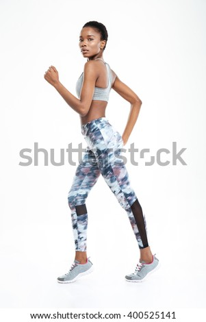 Full length portrait of afro american woman running isolated on a white background