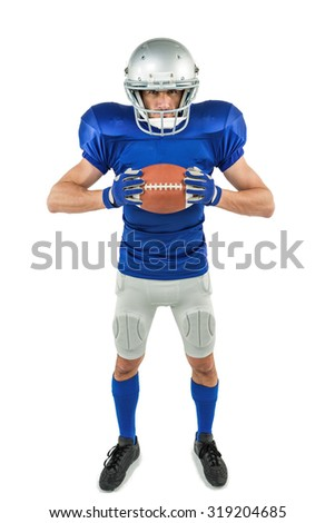 Full length portrait of American football player holding ball against white background - stock photo