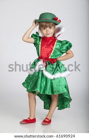 Full length portrait of an adorable little girl wearing green outfit and hat for Saint Patrick's Day, studio image - stock photo
