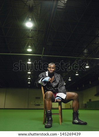 Full length portrait of an African American boxer sitting on chair - stock photo
