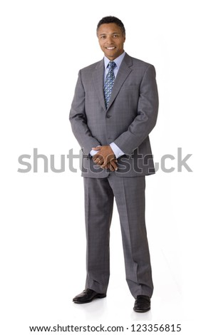 Full length portrait of an African American businessman smiling wearing a suit and tie isolated on a white background - stock photo