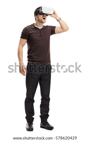 Full length portrait of an amazed guy using a virtual reality headset isolated on white background