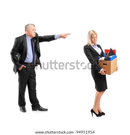 Full length portrait of an angry boss firing a woman in a suit carrying a box of personal items isolated on white background - stock photo