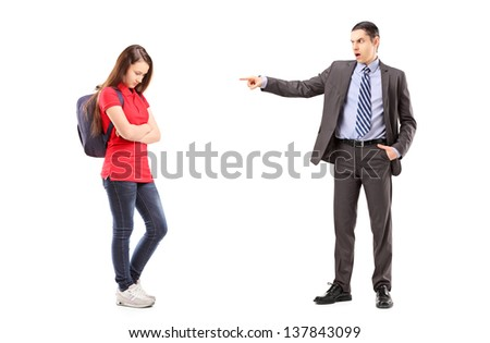 Full length portrait of an angry father shouting and pointing with his finger at his daughter, isolated on white background - stock photo