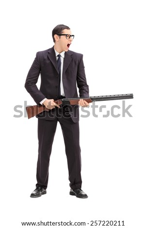 Full length portrait of an angry man holding a rifle and shouting isolated on white background - stock photo