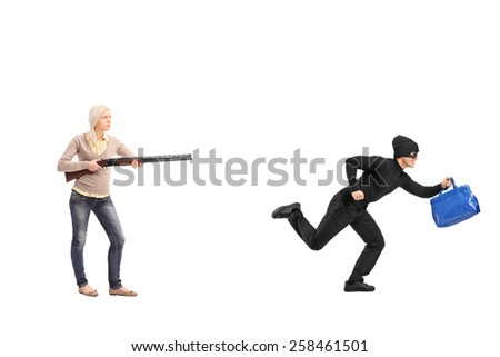 Full length portrait of an angry woman chasing a burglar with a shotgun isolated on white background - stock photo