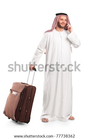 Full length portrait of an Arab tourist carrying a suitcase and talking on a mobile phone isolated on white background