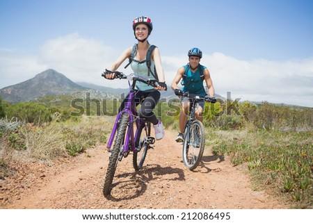 Full length portrait of an athletic couple mountain biking - stock photo
