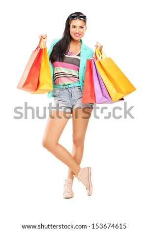 Full length portrait of an attractive casual female posing with shopping bags isolated on white background