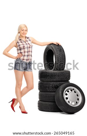 Full length portrait of an attractive female worker in a checkered shirt and glossy red high heels standing next to a stack of tires isolated on white background - stock photo