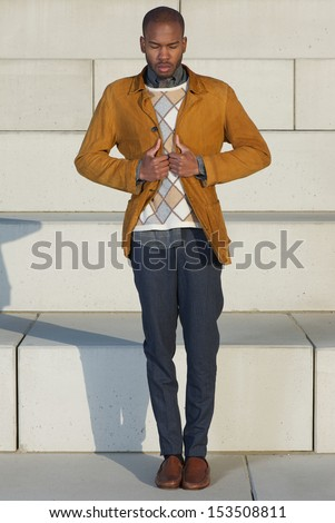 Full length portrait of an attractive male fashion model holding jacket outdoors - stock photo