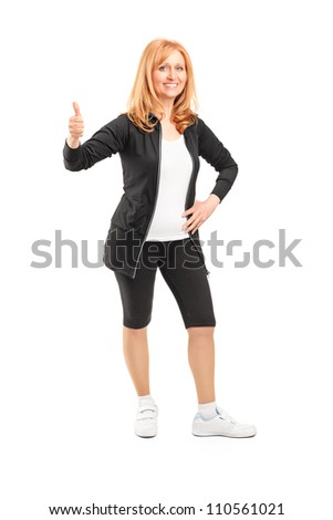 Full length portrait of an attractive middle-aged sportswoman giving the thumbs up isolated on white background - stock photo