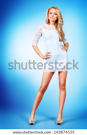 Full length portrait of an attractive young woman in white dress. - stock photo