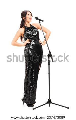 Full length portrait of an elegant female musician signing on a microphone isolated on white background - stock photo