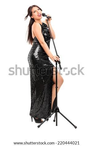 Full length portrait of an elegant female singer singing on microphone isolated on white background - stock photo