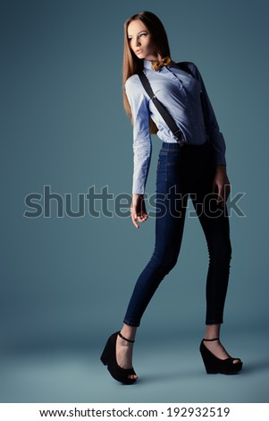 Full length portrait of an elegant girl model poses in blouse and bow tie. Refined style of old Europe.