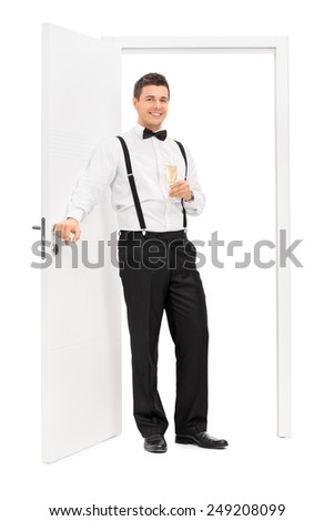 Full length portrait of an elegant guy standing by a door and holding a glass of wine isolated on white background - stock photo