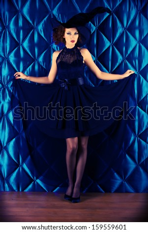 Full length portrait of an enchanting witch woman, beautiful and glamorous. Halloween.  - stock photo
