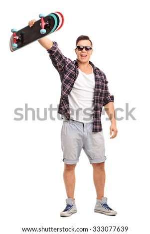 Full length portrait of an excited male skater holding his skateboard in the air and looking at the camera isolated on white background - stock photo