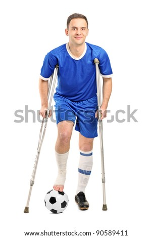 Full length portrait of an injured soccer football player on crutches isolated on white background - stock photo
