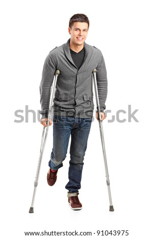 Full length portrait of an injured young man on crutches isolated on white background - stock photo