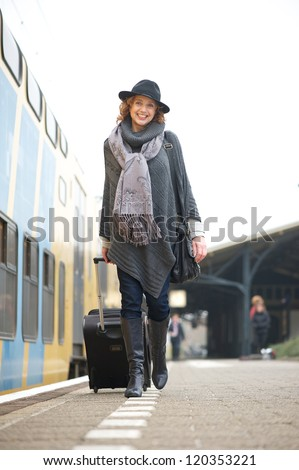 Full length portrait of an older woman walking on train platform with bag - stock photo