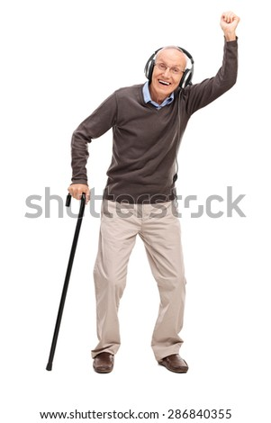 Full length portrait of an overjoyed senior holding a cane and listening to music on headphones isolated on white background - stock photo