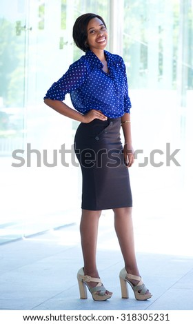 Full length portrait of an smiling african american business woman standing outside - stock photo