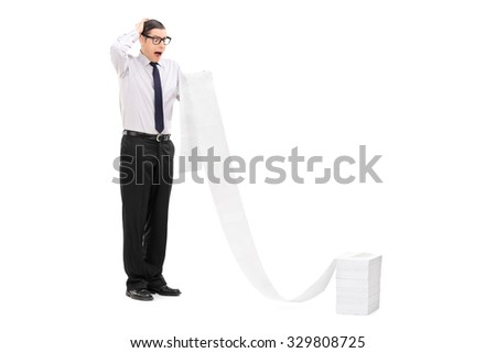 Full length portrait of an upset young businessman reading a long list stacked in front of him isolated on white background - stock photo