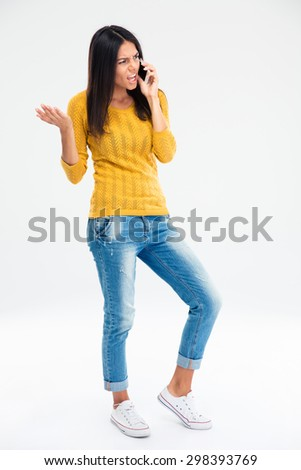 Full length portrait of angry woman in casual cloth talking on the phone isolated on a white background  - stock photo