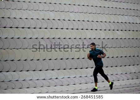 Full length portrait of athletic dark-skinned man running along beautiful grey wall outdoors, muscular build young runner working out while jogging in the park - stock photo