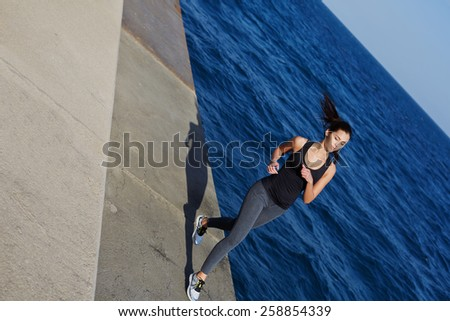 Full length portrait of athletic woman with beautiful figure running next to the ocean at sunny day, dynamic picture with sport girl working out with flying hair in action - stock photo