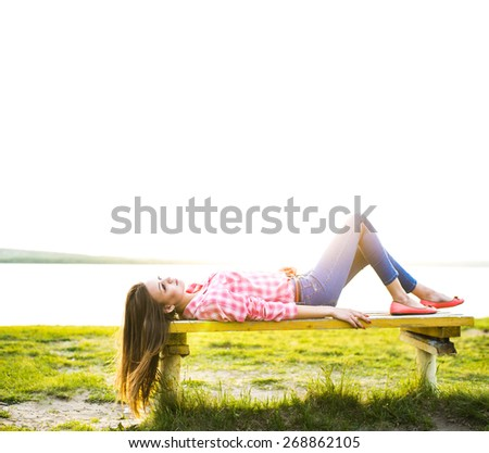 full length Portrait of Attractive caucasian girl with long brown hair Woman lie on bench at  beach against green fresh grass , sea and sunset sky background . Female on nature spring backdrop  - stock photo