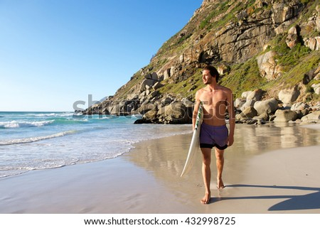 Full length portrait of attractive male surfer walking on beach with surfboard - stock photo