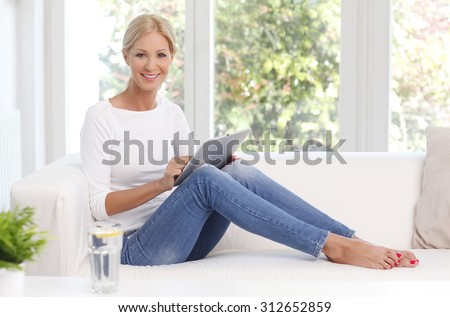 Full length portrait of attractive middle age woman holding hand digital tablet while sitting at sofa at living room and working online.