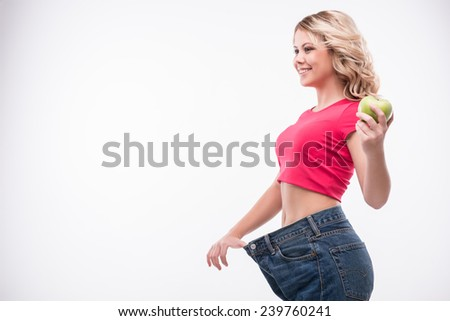 Full-length portrait of attractive slim young smiling woman in big jeans holding an apple showing successful weight loss  isolated on white background - stock photo